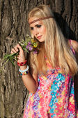 Beautiful blonde with flowers stand by tree — Stock Photo
