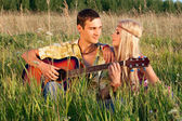 Cute young man and fine woman sit on meadow. young man plays gu — Stock Photo