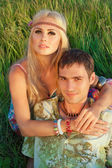 Cute young man and fine woman sit on meadow. — Stock Photo