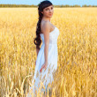Woman in white dress in field with wheat — Stock Photo