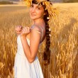 Young woman with chaplet in white dress standing in field - Stock Photo