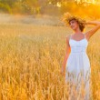 Young smiling woman in white dress standing in field - Stock Photo