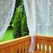Stock Photo: Wooden porch with lace curtains and garden view