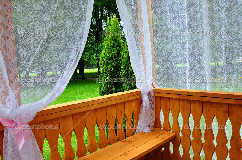 Wooden porch with lace curtains and garden view — Stock Photo #11331968