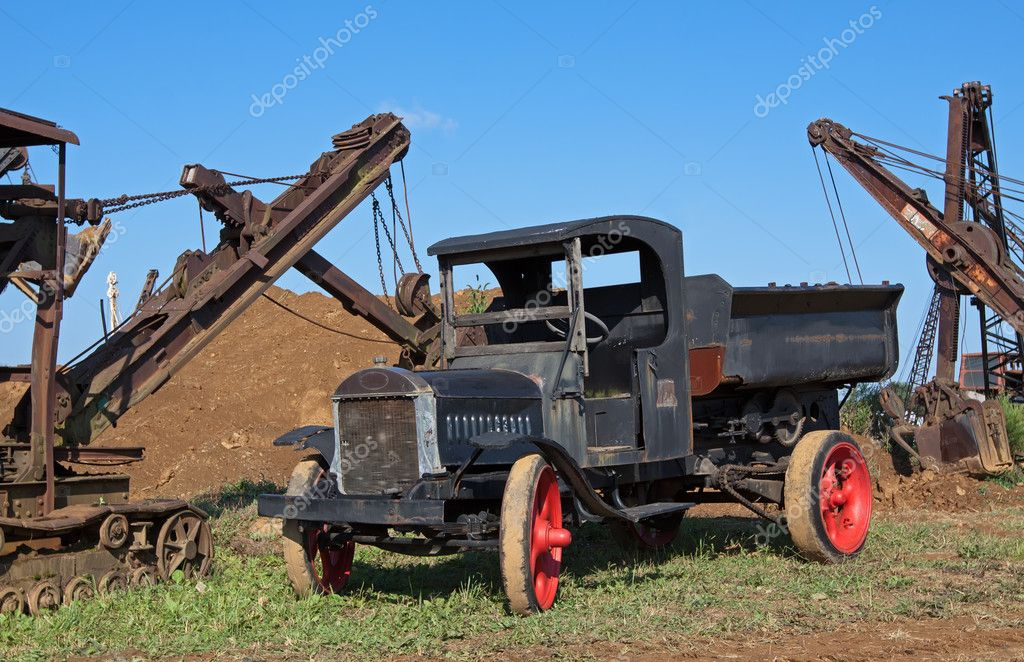 An old dump truck in a field with excavating equipment  Stock Photo #12369637