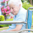 Senior lady in wheel chair in front of house — Foto de Stock