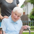 Happy senior lady in wheelchair with caregiver — Stock Photo