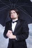 Homme avec parapluie sous la pluie et de soupirs — Photo