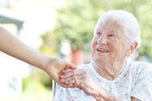 Senior mujer tomados de la mano con el portero — Foto de Stock