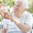 Senior Woman Holding Hands with Caretaker - Stock Photo