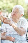 Mulher sênior de mãos dadas com o zelador — Foto Stock