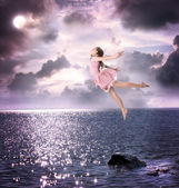 Little girl jumping into the night sky — Stock Photo