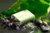 Bar of soap with flowers and calla leaf — Stock Photo