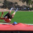 Young teenager on high jump competition — Stock Photo
