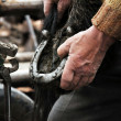 A farrier blacksmith hooves a horseshoe — Stock Photo