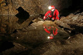 A speleologist reflection in cave water — Stock Photo