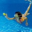 Happy smiling underwater child in swimming pool — Stock Photo #10765519