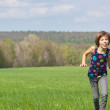 Happy active girl running on green field — Stock Photo #10765598