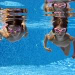 Happy smiling underwater children in swimming pool — Stock Photo #10765758