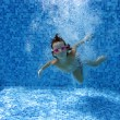 Happy underwater child jumping in swimming pool - Stock Photo