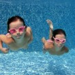 Happy smiling underwater children in swimming pool — Stock Photo #10765904