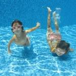 Happy smiling underwater children in swimming pool — Stock Photo #10765934