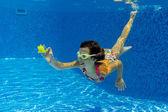 Happy smiling underwater child in swimming pool — Stock Photo