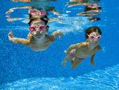 Happy smiling underwater children in swimming pool — Stock Photo