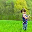 Kid with flowers having fun outdoors on green field — Stock Photo