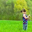 Kid with flowers having fun outdoors on green field - Stock Photo