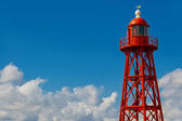 Red lighthouse on blue sky background — Stock Photo