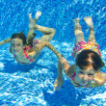 Happy smiling underwater children in swimming pool — Stock Photo #11960490