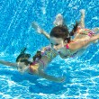 Happy smiling underwater children in swimming pool - Stock Photo