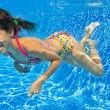 Happy smiling underwater child in swimming pool - Stock Photo