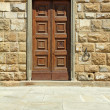 Elegant wooden door and stone wall — Stock Photo
