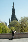 Scottish Piper playing with Edinburgh city background in May 2012 — Stok fotoğraf
