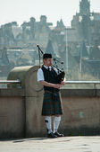 Scottish Piper playing with Edinburgh city background in May 2012 — Stock Photo