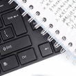 Stock Photo: Notepad and pen on keyboard