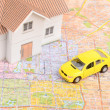 Toy car and house model on map — Stock Photo #12145560