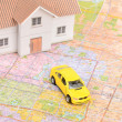 Toy car and house model on map — Stock Photo