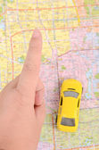 Toy car and map with finger — Stock Photo