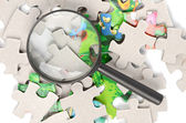 Puzzles and magnifier — Stock Photo