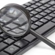 Computer keyboard and magnifier — Stock Photo