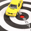 Toy car on dart board — Stock Photo