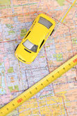 Toy car and steel tape on map — Stock Photo