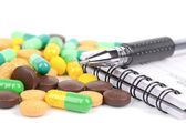 Medicine and notepad with pen — Stock Photo