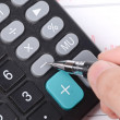 Calculator and pen on stock graph — Stock Photo #12391299