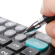 Calculator and pen on stock graph — Stock Photo #12391313