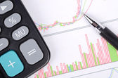 Calculator and pen on stock graph — Stock Photo