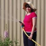 Beautiful young girl watering garden — Foto de Stock   #11330198